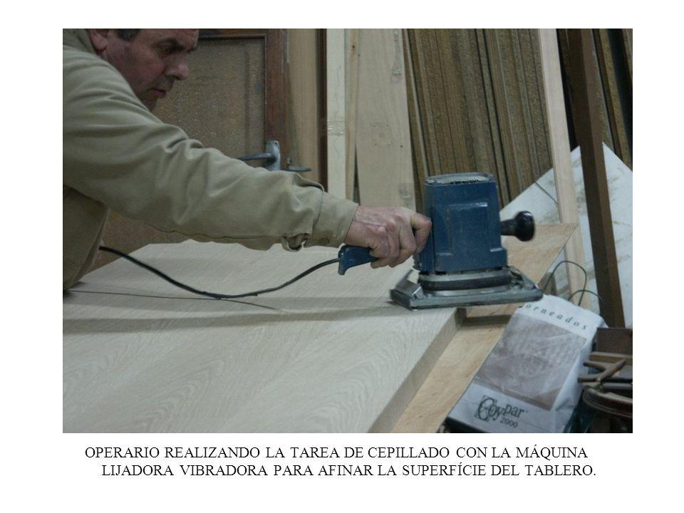OPERARIO REALIZANDO LA TAREA DE CEPILLADO CON LA MÁQUINA LIJADORA VIBRADORA PARA AFINAR LA SUPERFÍCIE DEL TABLERO.