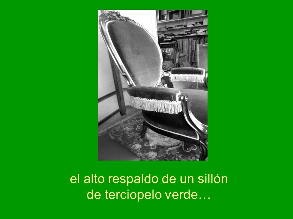 el alto respaldo de un sillón de terciopelo verde…