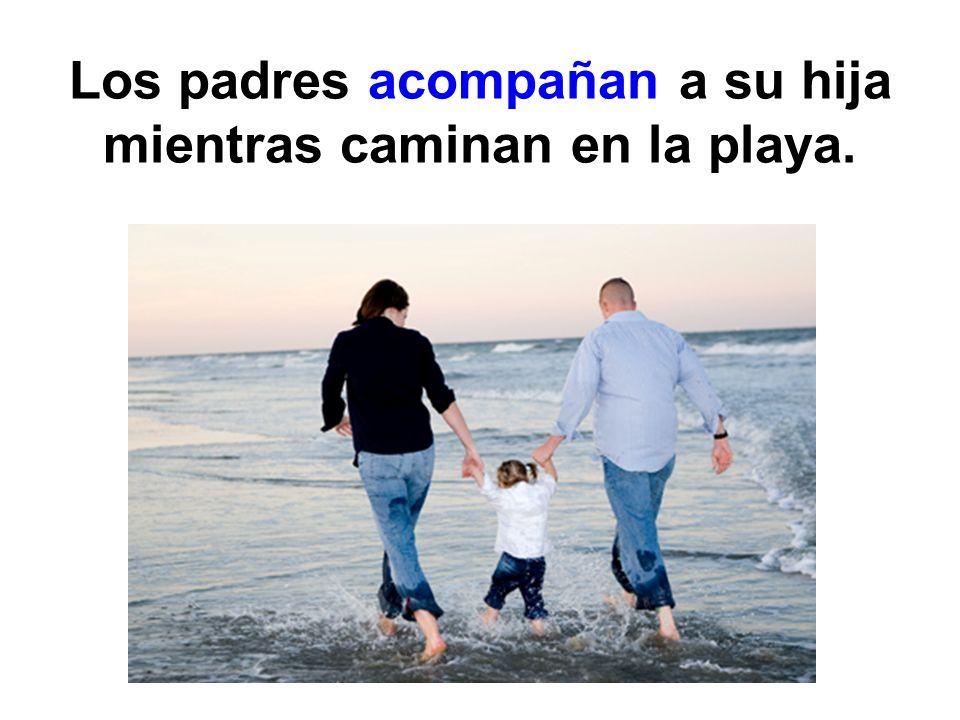 Los padres acompañan a su hija mientras caminan en la playa.
