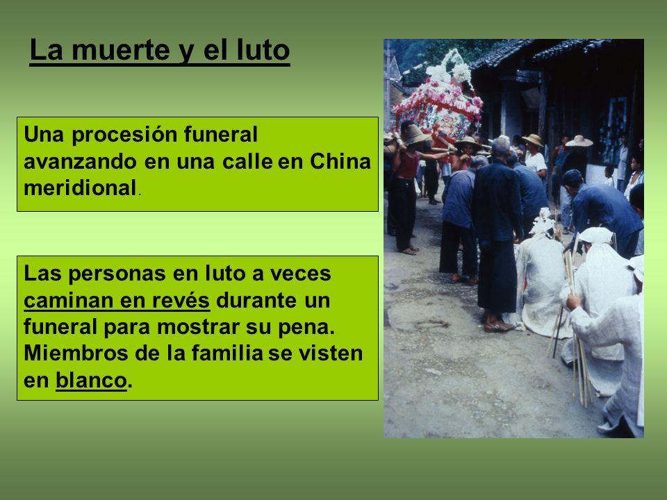 La muerte y el luto Una procesión funeral avanzando en una calle en China meridional.