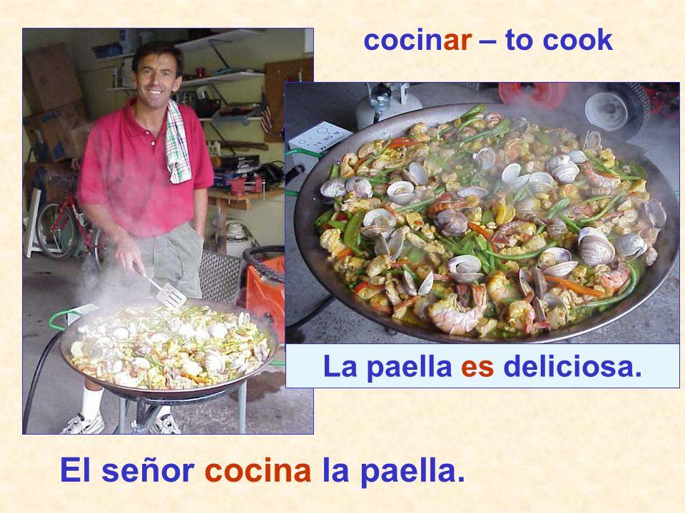 El señor cocina la paella.