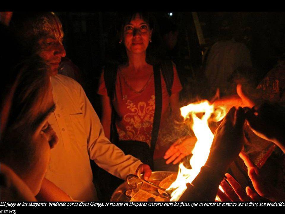 El fuego de las lámparas, bendecido por la diosa Ganga, se reparte en lámparas menores entre los fieles, que al entrar en contacto con el fuego son bendecidos