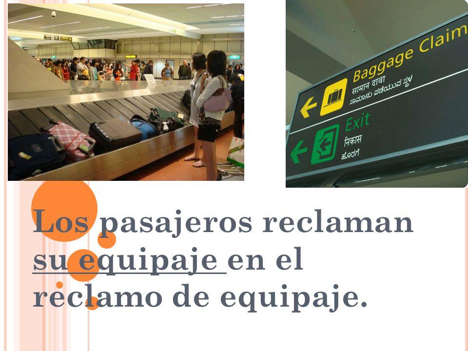 Los pasajeros reclaman su equipaje en el reclamo de equipaje.