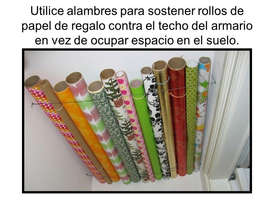 Utilice alambres para sostener rollos de papel de regalo contra el techo del armario en vez de ocupar espacio en el suelo.