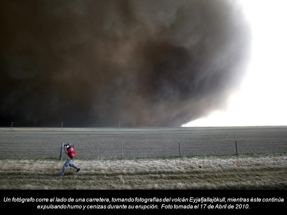 Un fotógrafo corre al lado de una carretera, tomando fotografías del volcán Eyjafjallajökull, mientras éste continúa expulsando humo y cenizas durante su erupción.