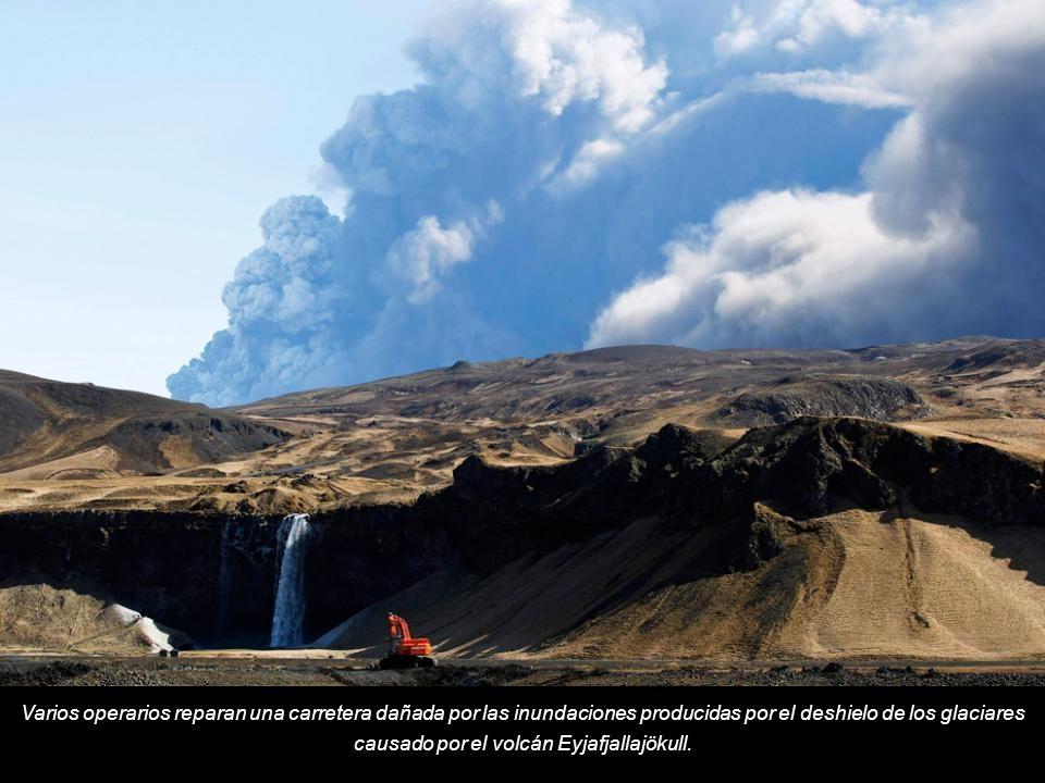 Varios operarios reparan una carretera dañada por las inundaciones producidas por el deshielo de los glaciares causado por el volcán Eyjafjallajökull.
