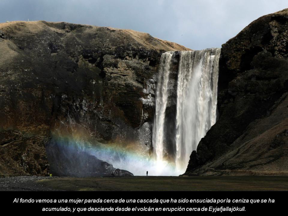 Al fondo vemos a una mujer parada cerca de una cascada que ha sido ensuciada por la ceniza que se ha acumulado, y que desciende desde el volcán en erupción cerca de Eyjafjallajökull.