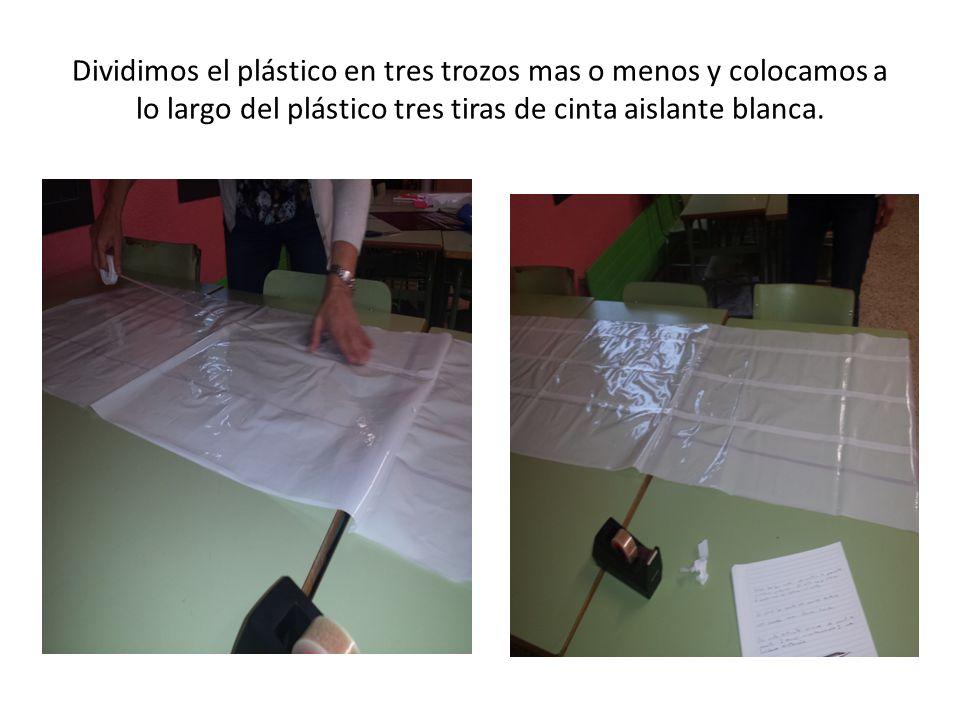 Dividimos el plástico en tres trozos mas o menos y colocamos a lo largo del plástico tres tiras de cinta aislante blanca.