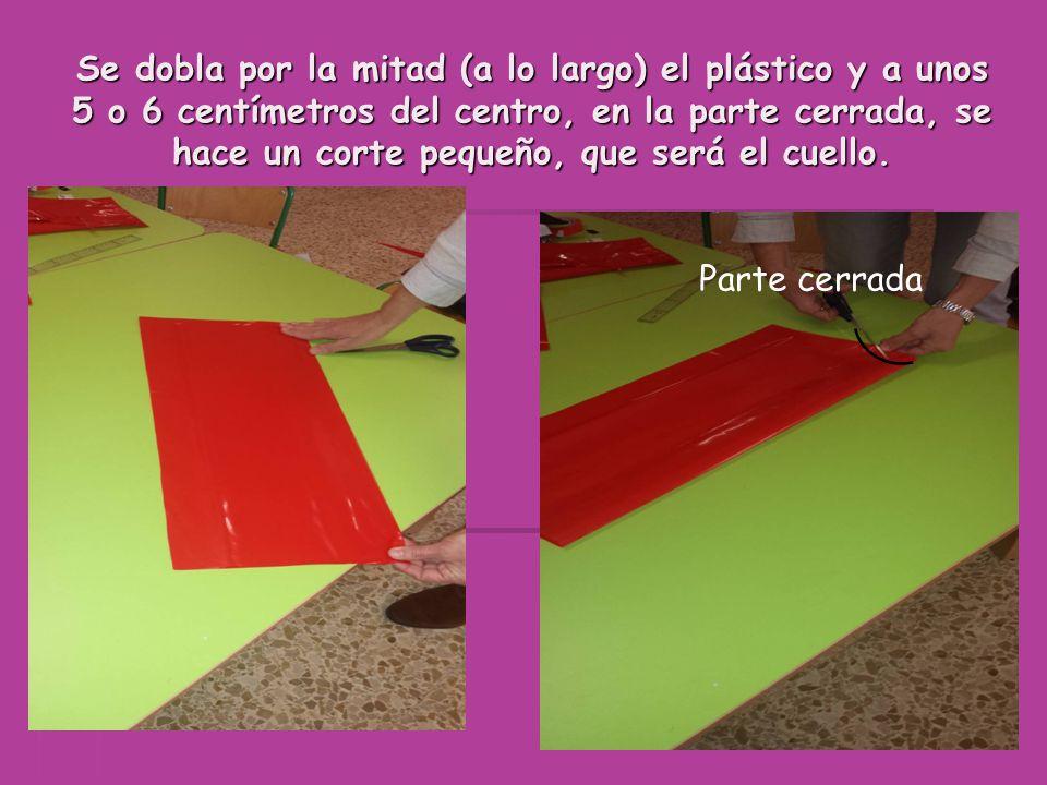 Se dobla por la mitad (a lo largo) el plástico y a unos 5 o 6 centímetros del centro, en la parte cerrada, se hace un corte pequeño, que será el cuello.