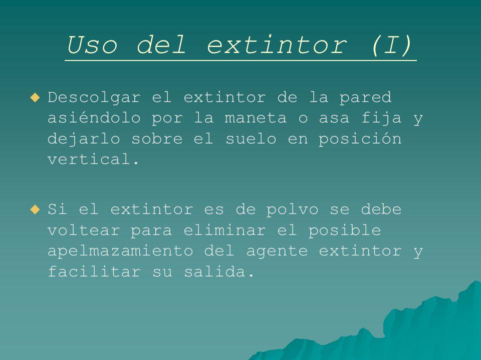 Uso del extintor (I) Descolgar el extintor de la pared asiéndolo por la maneta o asa fija y dejarlo sobre el suelo en posición vertical.