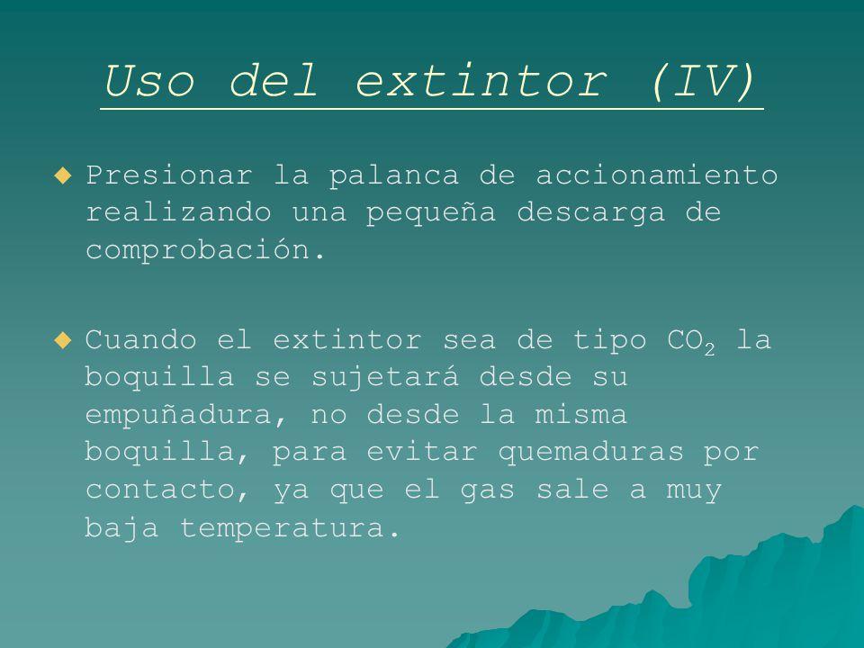 Uso del extintor (IV) Presionar la palanca de accionamiento realizando una pequeña descarga de comprobación.