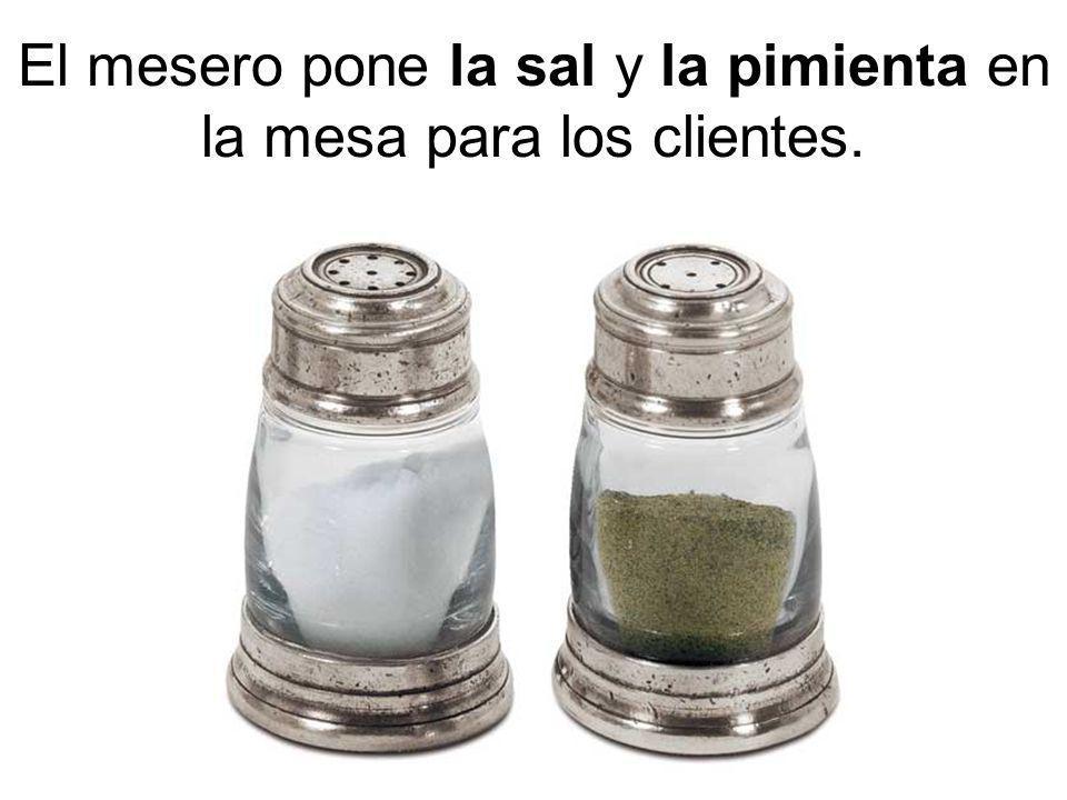 El mesero pone la sal y la pimienta en la mesa para los clientes.