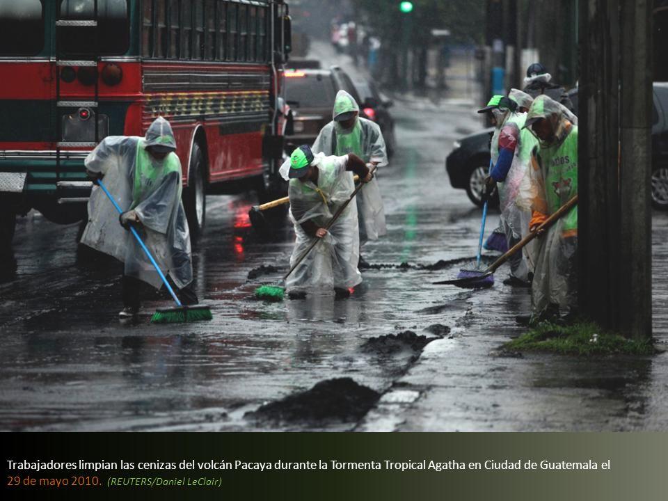 Trabajadores limpian las cenizas del volcán Pacaya durante la Tormenta Tropical Agatha en Ciudad de Guatemala el