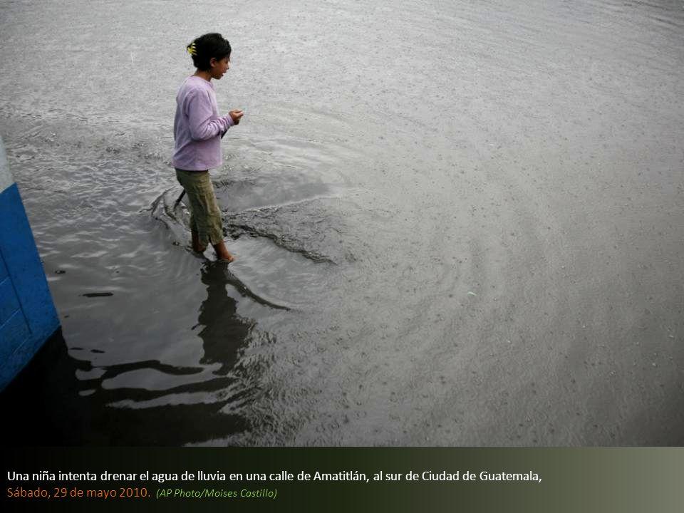 Una niña intenta drenar el agua de lluvia en una calle de Amatitlán, al sur de Ciudad de Guatemala,
