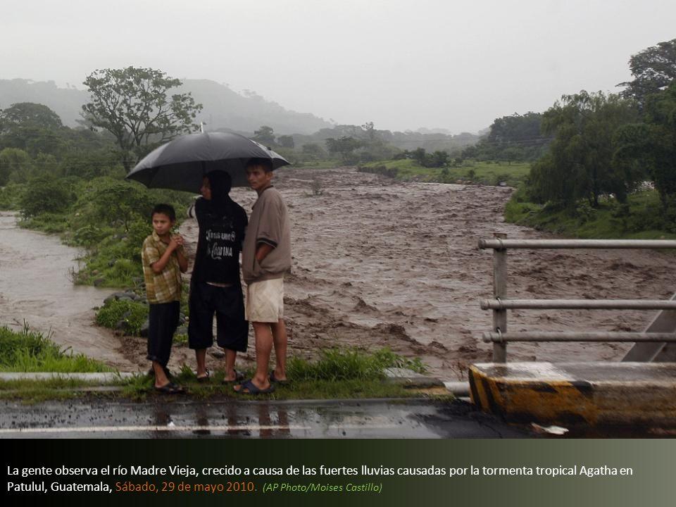 La gente observa el río Madre Vieja, crecido a causa de las fuertes lluvias causadas por la tormenta tropical Agatha en Patulul, Guatemala, Sábado, 29 de mayo 2010.
