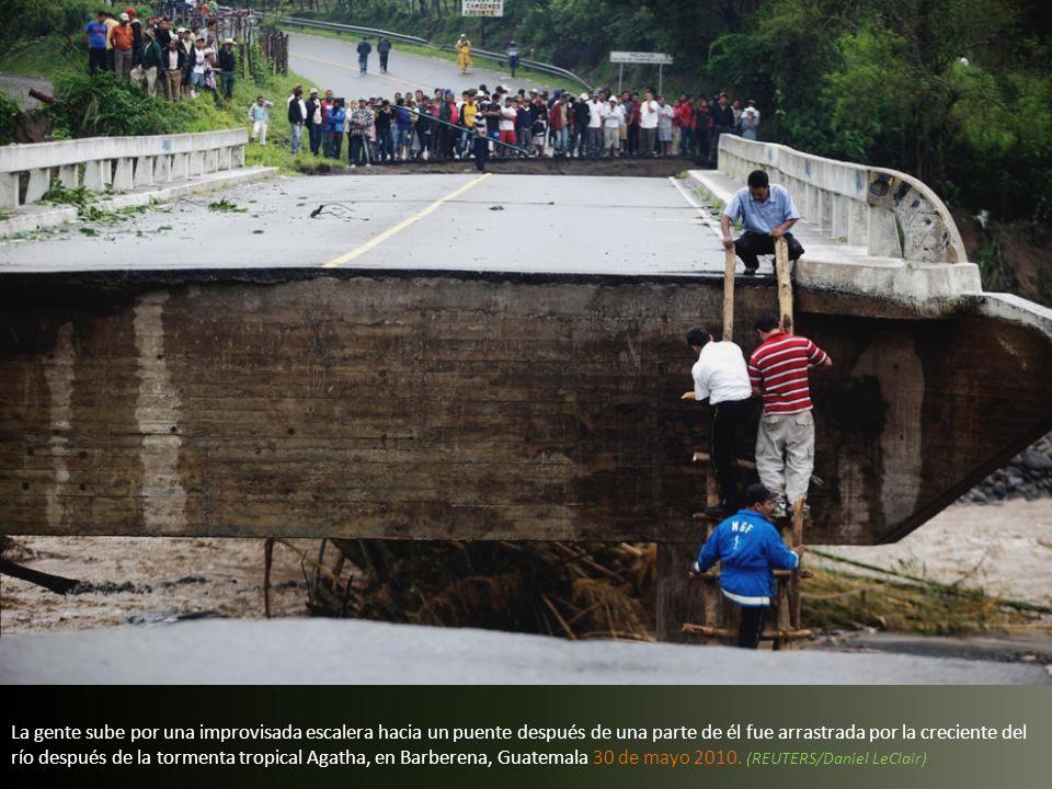 La gente sube por una improvisada escalera hacia un puente después de una parte de él fue arrastrada por la creciente del río después de la tormenta tropical Agatha, en Barberena, Guatemala 30 de mayo 2010.