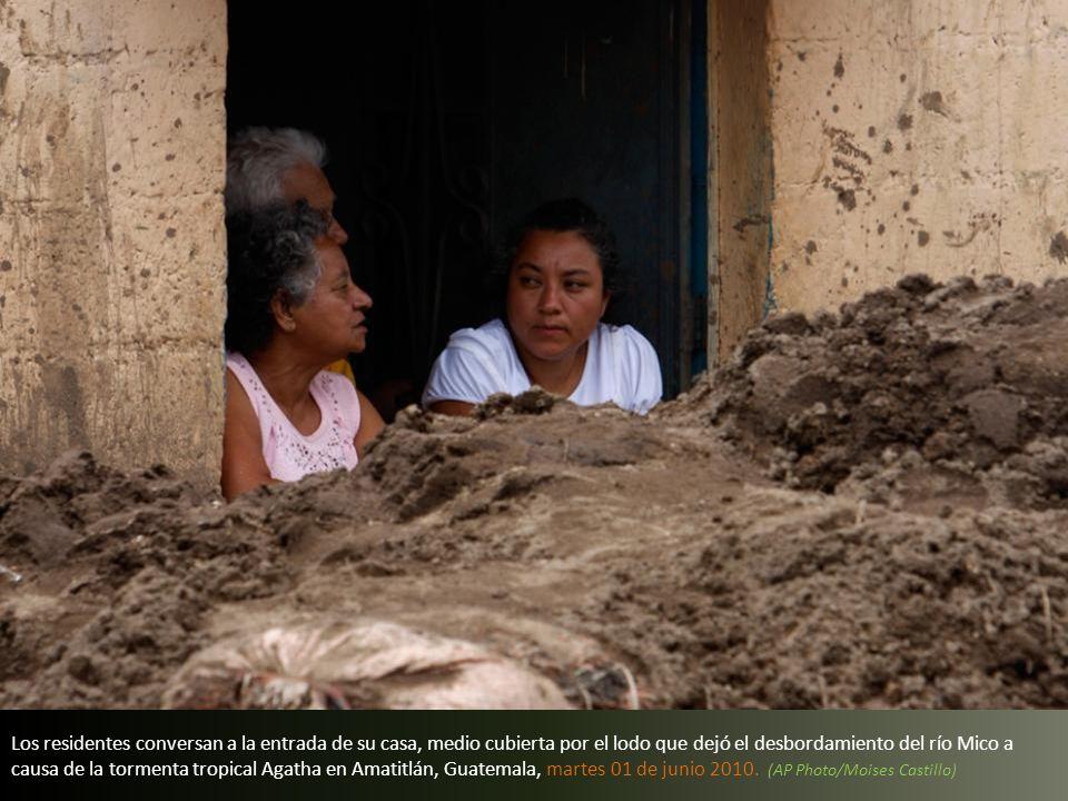 Los residentes conversan a la entrada de su casa, medio cubierta por el lodo que dejó el desbordamiento del río Mico a causa de la tormenta tropical Agatha en Amatitlán, Guatemala, martes 01 de junio 2010.