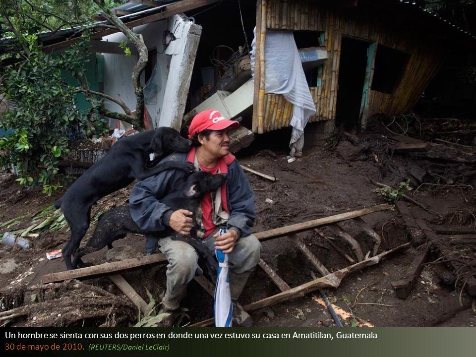 Un hombre se sienta con sus dos perros en donde una vez estuvo su casa en Amatitilan, Guatemala
