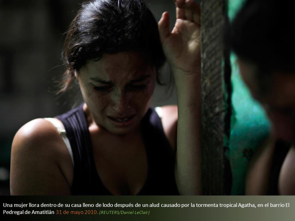 Una mujer llora dentro de su casa lleno de lodo después de un alud causado por la tormenta tropical Agatha, en el barrio El Pedregal de Amatitlán 31 de mayo 2010.