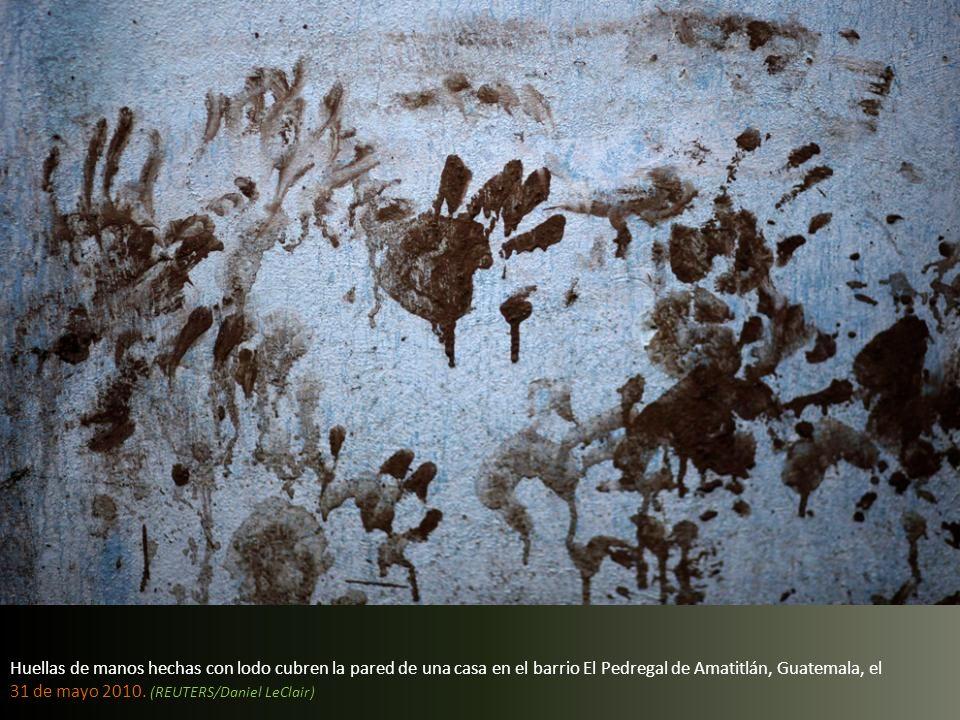 Huellas de manos hechas con lodo cubren la pared de una casa en el barrio El Pedregal de Amatitlán, Guatemala, el