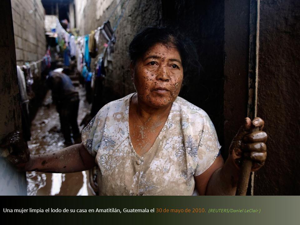 Una mujer limpia el lodo de su casa en Amatitilán, Guatemala el 30 de mayo de 2010.