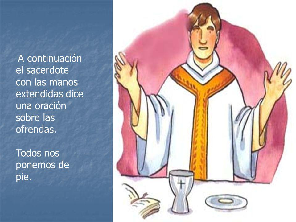 con las manos extendidas dice una oración sobre las ofrendas.