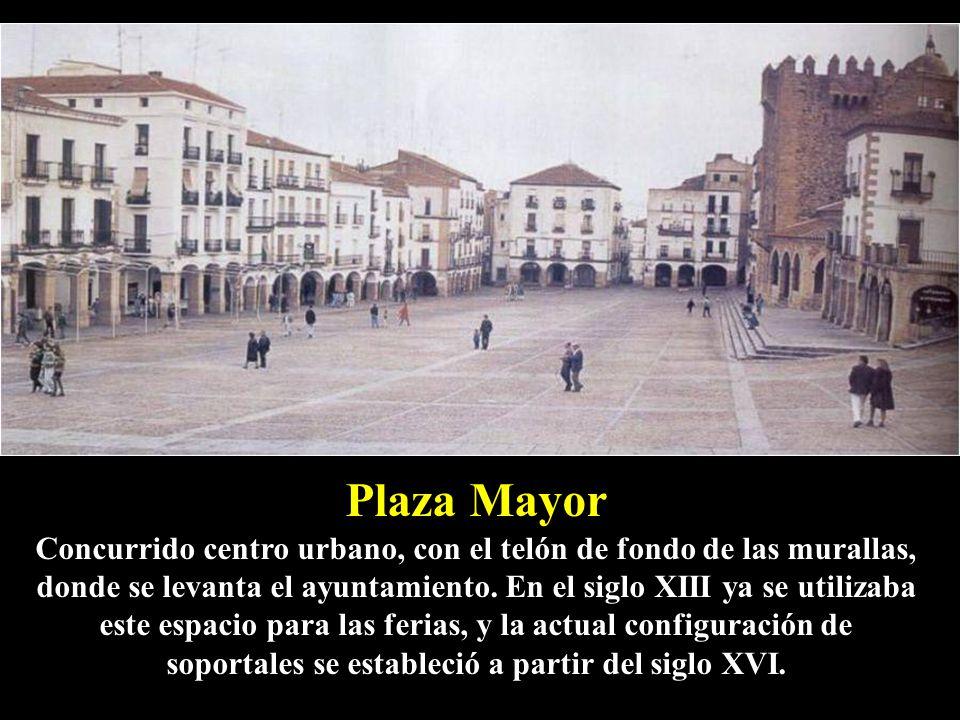 Plaza Mayor Concurrido centro urbano, con el telón de fondo de las murallas, donde se levanta el ayuntamiento.