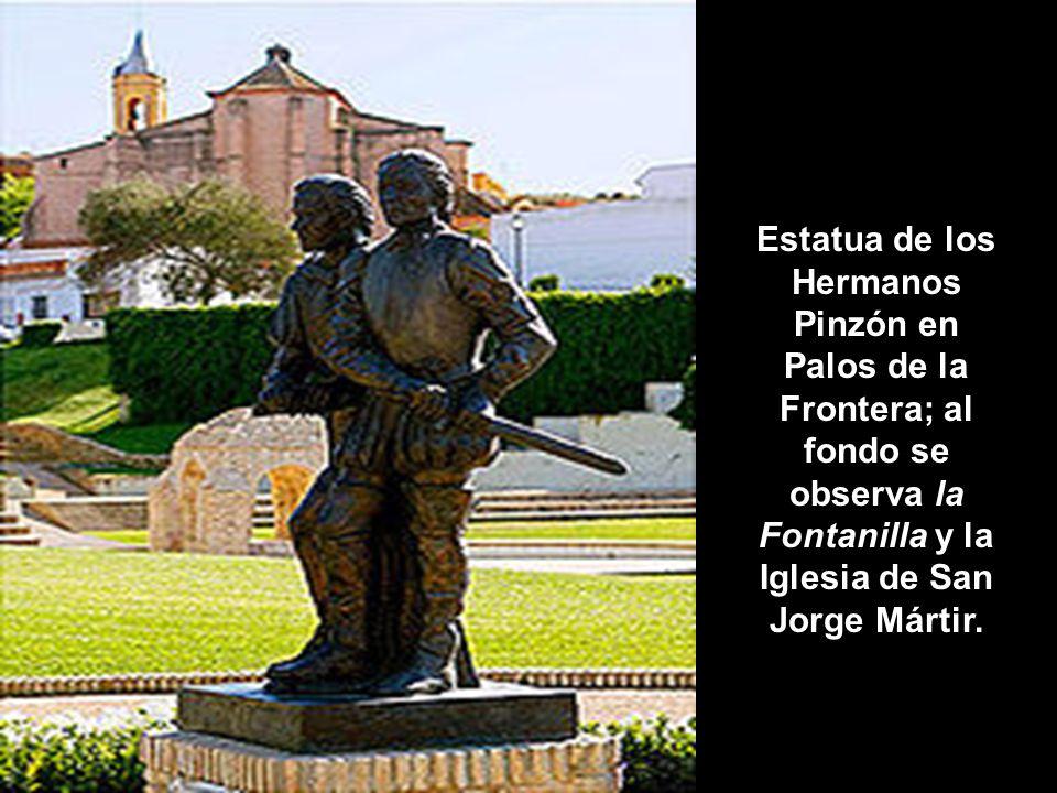 Estatua de los Hermanos Pinzón en Palos de la Frontera; al fondo se observa la Fontanilla y la Iglesia de San Jorge Mártir.