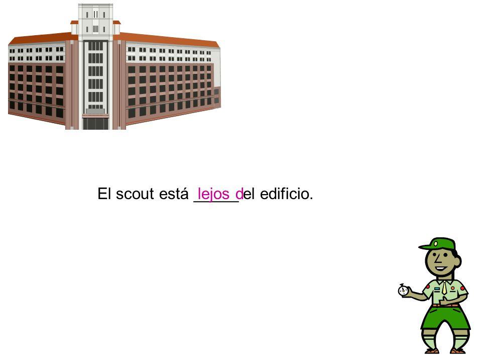 El scout está _____ el edificio.