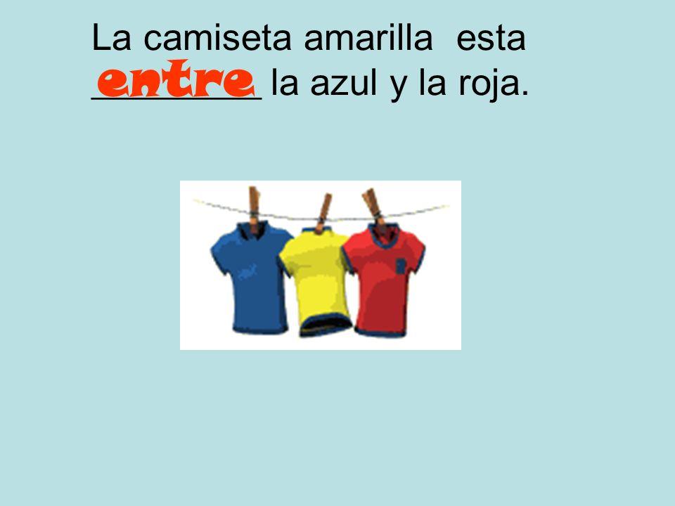 La camiseta amarilla esta _________ la azul y la roja.