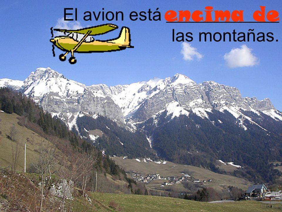 encima de El avion está _____________ las montañas.