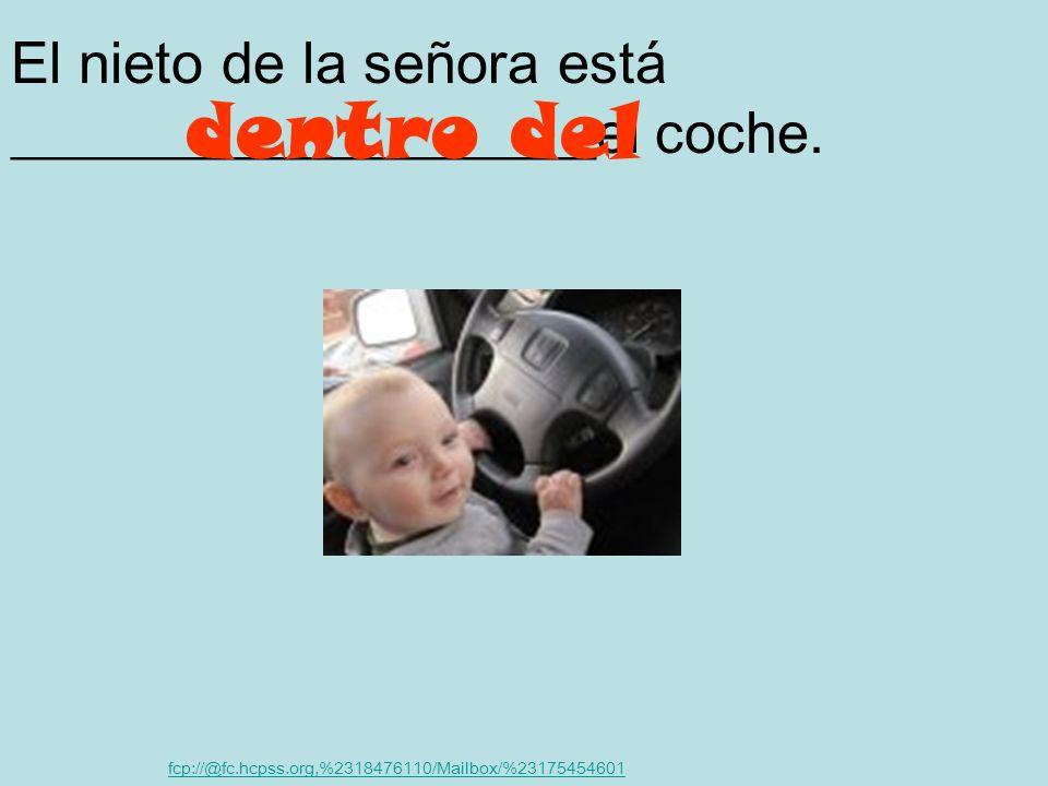 El nieto de la señora está ____________________el coche.